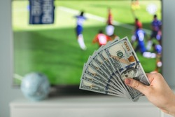The winner at football betting holds a dollar money prize in hand near the TV