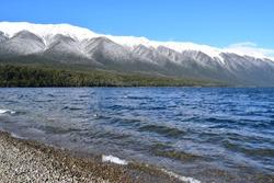 The winter landscape and choppy waters of Lake Rotoiti in the Tasman Region of New Zealand.