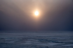 The winter sun in the mist over the frozen sea.Snowy patterns outdoor.Soft sunlight falls on the surface of the ice.