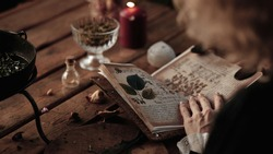 the witch cooks an elixir with herbs in a cauldron, recipe book
