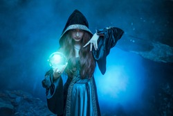 The witch with magic ball in her hands causes a spirits in cave