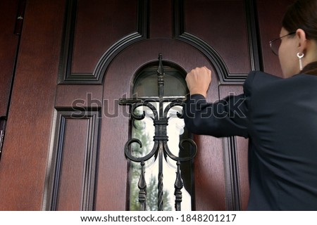The woman and the state structure are persistently knocking on the door of a private house. Civil servant with a summons