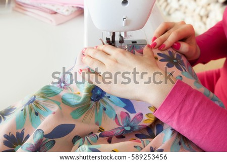 The woman at the sewing machine sews. Cabinet craftswomen and seamstresses. Workshop with tissues. #589253456
