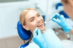 The woman came to see the dentist. She sits in the dental chair. The dentist bent over her. Happy patient and dentist concept.