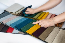 The woman chooses a fabric in the catalog with fabrics with different colors and different textures for a new sofa, the woman compares colors and quality of fabric. Copy space