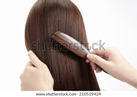 The Woman Combing Her Hair With A Hairbrush