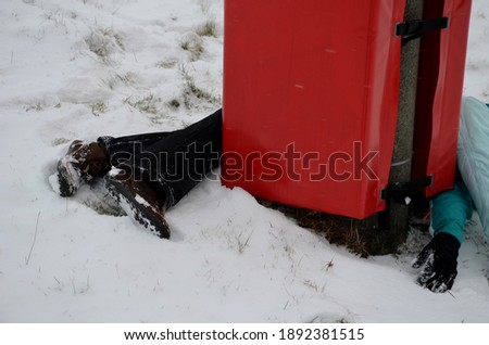 The woman crashed at high speed into a foam barrier on a pole near the ski slope. She is injured, but saved by a red protective mattress, an impact zone. lying on the snow around the pole. Stock fotó ©