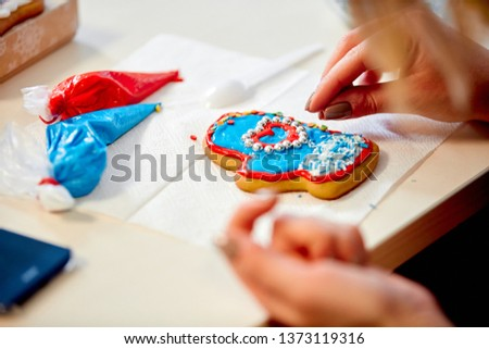the woman decorates gingerbread in the form of mittens on a napkin on the table #1373119316