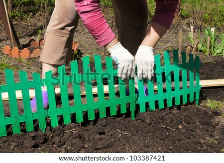 the woman establishes a green plastic fencing on a flower bed
