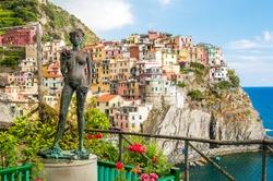 The woman grape, bronze statue by Antonio Puja and view of Manarola. La Spezia, Cinque Terre, Italy