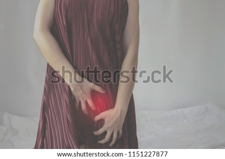 The woman has itching on his genitals.Asian women wear red clothes on their bed, they have itching in the vagina.Girl hands placed at the vagina.Do not focus on objects.