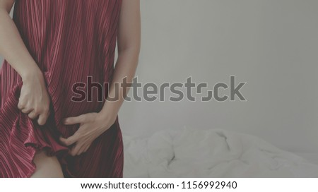 The woman has itching on his genitals. Asian women wear red clothes on their bed, they have itching in the vagina.Girl hands placed at the vagina.Do not focus on objects.