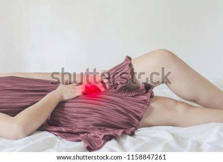 The woman has itching on his genitals. Asian women wear red clothes on their bed, they have itching in the vagina.Girl hands placed at the vagina.