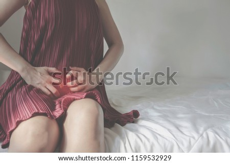 The woman has itching on his genitals. Asian women wear red clothes on their bed, they have itching in the vagina. Girl hands placed at the vagina.Do not focus on objects.