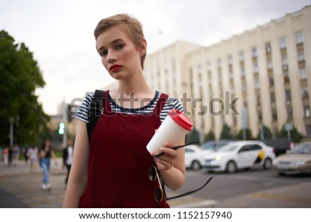 the woman holds out a cup with a drink in her hand                            #1152157940
