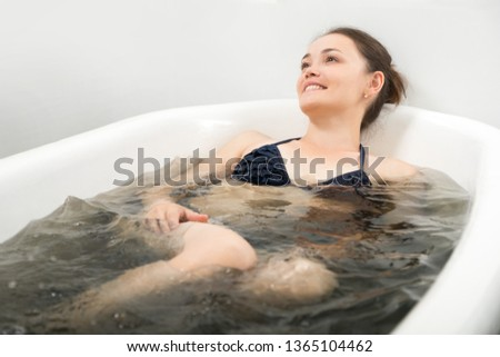 the woman in a bathing suit lies in bromine - an iodic bathtub