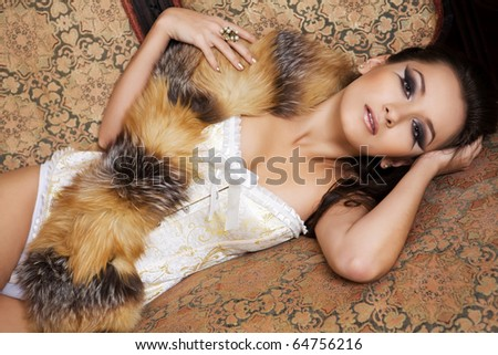 The woman in a corset and with fur. The glamour woman in underwear in an interior.