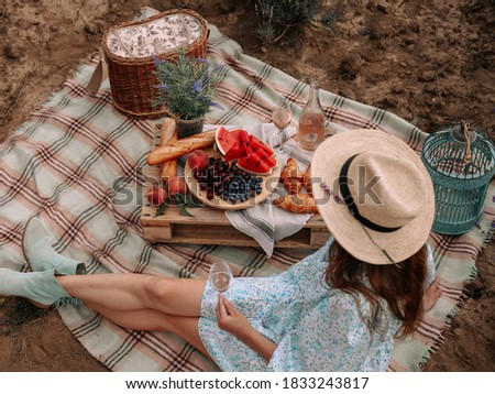 The woman in a straw hat has a summer picnic in nature with fruit and pink wine. Beautifully decorated picnic in Rustic style. Stockfoto ©