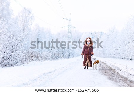 The woman in fur coat walk with dog