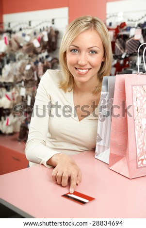 The woman in shop with packages smiles and holds in a hand a credit card