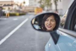 The woman in the car looking at the side mirror.