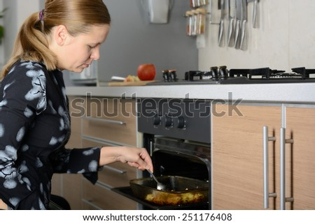 The woman in the kitchen preparing the potatoes in the oven