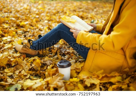 The woman in yellow coat, jeans and boots sitting under the maple tree with a red book and cup of coffee or tea in fall city park on a warm day. Autumn golden leaves. Reading concept. Close up.