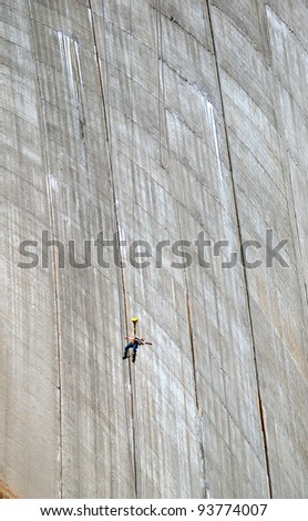 The woman is bungee jumping along the concrete wall. The Contra Dam is a popular bungee jumping venue in the Swiss Alps.