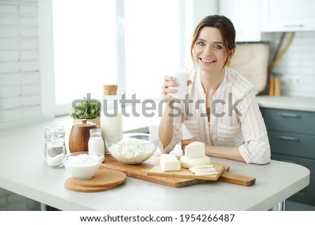 The woman is drinking milk in her kitchen. High quality photo. Foto stock ©