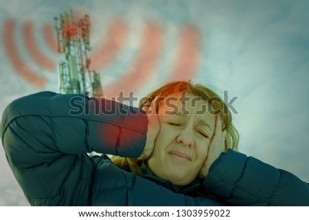 The woman is holding her head near the BTS. Harmful radiation from cellular network transmitters concept