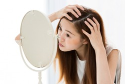 The woman is looking at her scalp in the mirror.