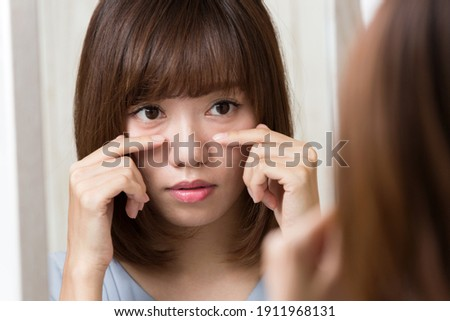 The woman is looking in the mirror and touching her lower eyelids. Photo stock ©