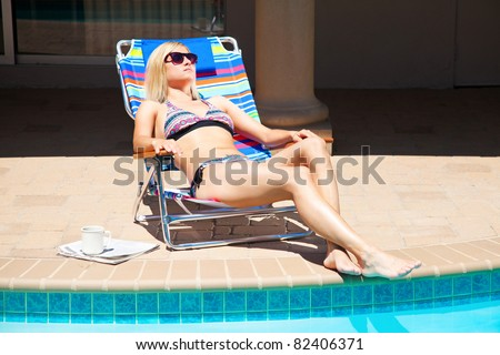 The woman is sitting near the pool