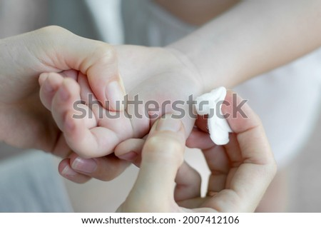 The woman is trying to pull the splinter out of the child's hand. A splinter in a child's hand Stock photo ©