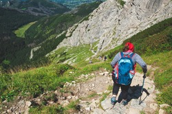 The woman is walking along the path over the precipice. Extreme hiking trail. Beautiful but dangerous tourist place in mountain. Huge rocks of the Small Giewont peak in the Tatra Mountains, Poland.