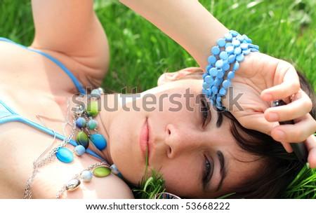 The woman lies on a green grass. Summer.