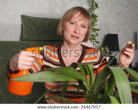 The woman looks after indoor plants by means of a spray