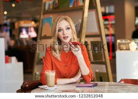 The woman looks away, seriously dictates to the client information, sitting in a cafe. A beautiful girl with blond wavy hair is dictates an audio message on the phone.