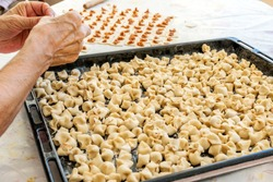 The woman making meaty ravioli (Turkish: manti). Manti in Asian cuisines are usually larger in size. They are steamed in a multi level metal steamer called mantovarka, mantyshnitsa, manti kazan.