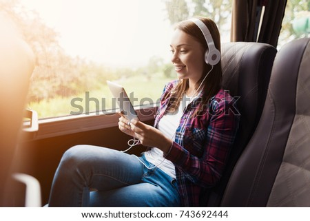 The woman on the passenger seat of the bus listens to music and looks at the tablet. She looks at the device's screen and smiles. Outside the window is a beautiful green landscape.