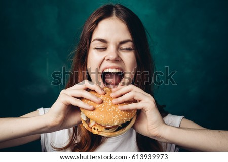 The woman opened her mouth to eat a hamburger, a hamburger in her hands, a woman with a hamburger #613939973
