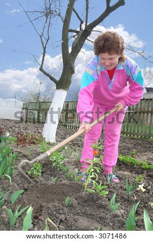 The woman plants flowers in a kitchen garden