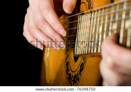 The woman plays an acoustic guitar close-up