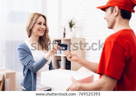 The woman received the parcel from the delivery worker. The woman pays the deliverer. A man in red clothes brought a package to a young woman. A woman pays a man a bank card.