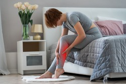 The woman's calf muscle cramped, massage of female leg in home interior, painful area highlighted in red