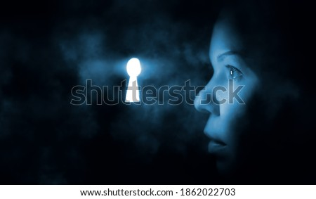 the woman's face in the dark looks through the keyhole glowing blue mysterious light Сток-фото ©