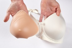 The woman shows a silicone breast prosthesis before inserting it into the white technical bra.