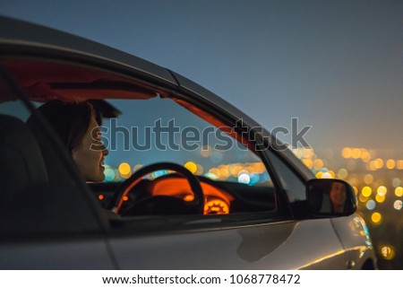 The woman sit in a car on the city lights background. evening night time #1068778472