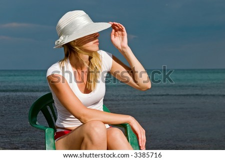 The woman sits on a sea background