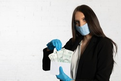 The woman slips a bundle of one hundred Polish zloty banknotes into a white envelope.